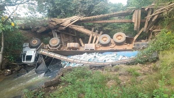Caminhão carregado de ração cai dentro de rio após ponte de madeira desabar