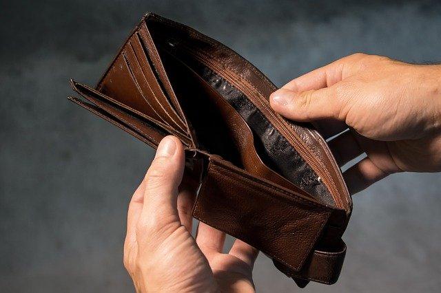 mãos abrindo uma carteira vazia