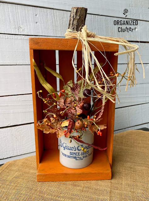 Photo of a crate pumpkin holding fall foliage