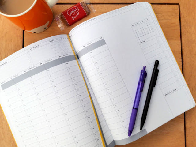 A double page spread from inside the planner showing the weekly view and space for lists.  There is an orange mug, some pens and a biscuit on the table.