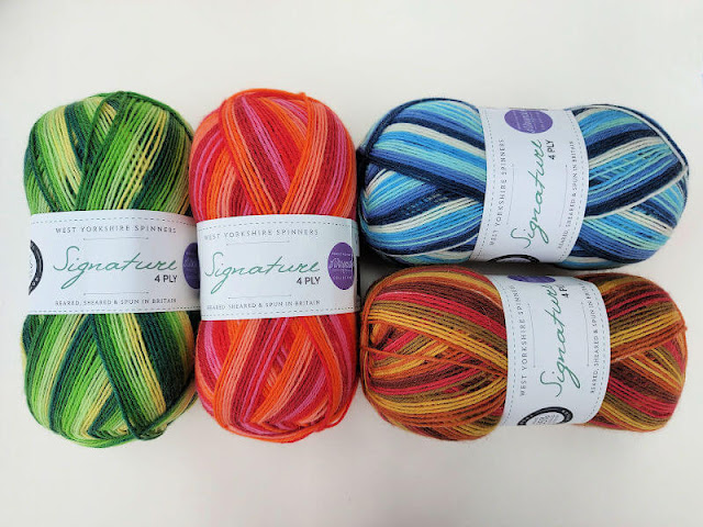 Four balls of yarn - one green striped, one pink striped, one blue striped and one brown striped on a cream background,