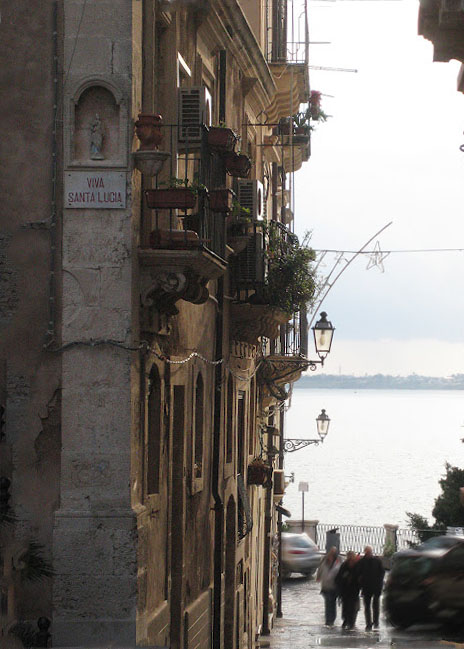 A sloping street that leads to the sea in Ortigia, Sicily.  In the side of the building that lines the street, a small statue and plaque that reads Viva Santa Lucia.