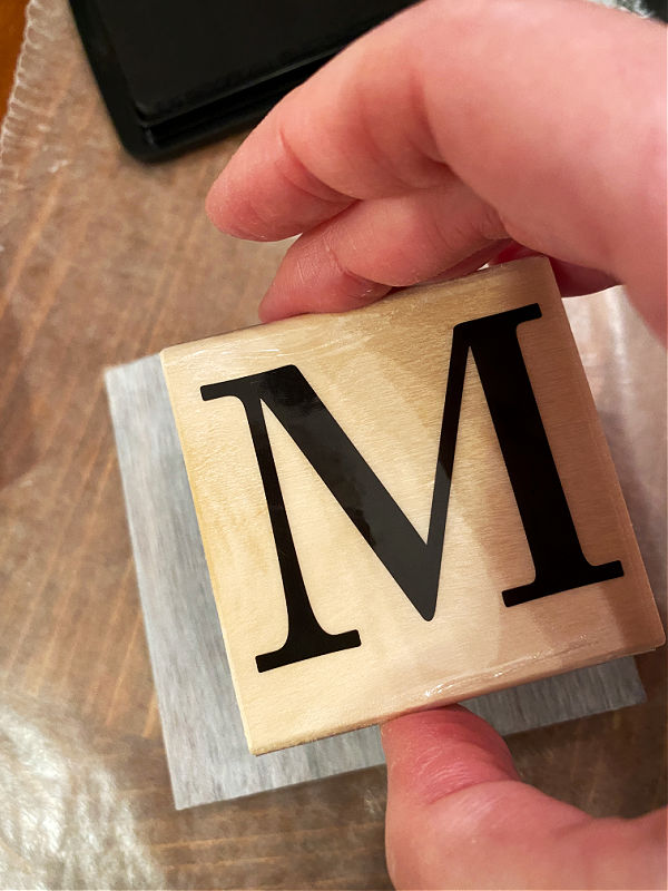 Monogram M Stamp being placed on a tile