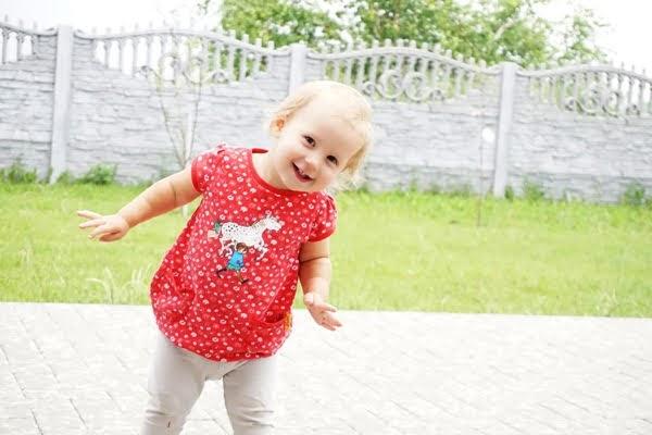 Uśmiechnięta dziewczynka w ogrodzie