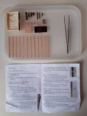 Pieces of a 1/12 scale miniature kit laid out neatly on a small tray next to a pair of tweezers. Next to the tray is a set of instructions for the kit.