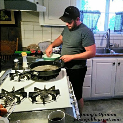 My son Tim cracking eggs into a bowl to scramble, standing next to the kitchen stove with a frying pan on top.