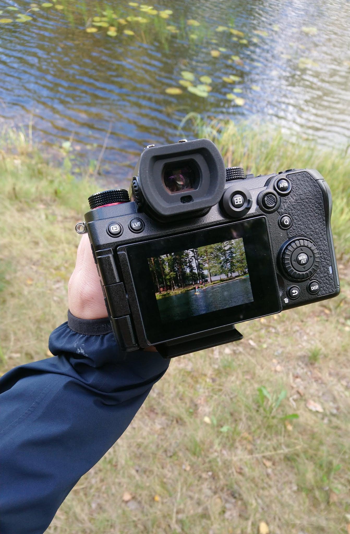 Kuvassa käsi pitää kameraa, jolla on valokuvattu
