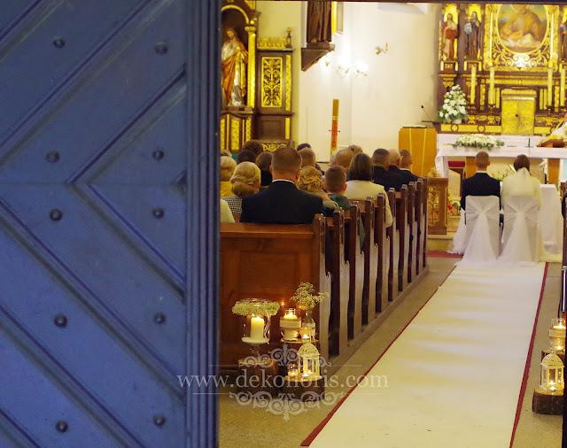 Rustykalna dekoracja ślubna wejście do kościoła świece, pieńki i gipsówka Prudnik