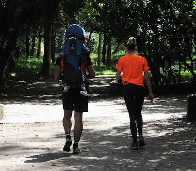 Casal caminhando com o filho nas costas