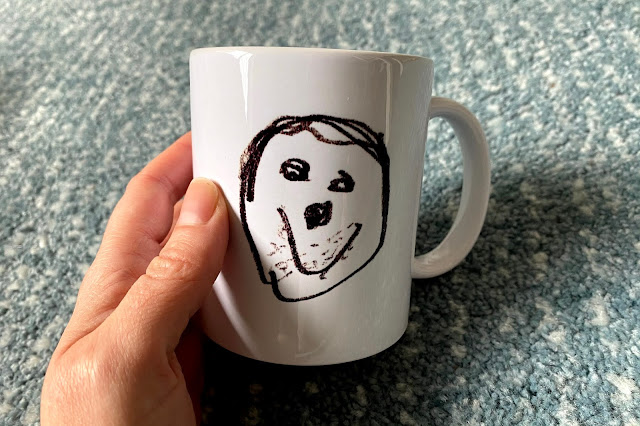 A drawing of a face by a 5 year old on the side of a white mug