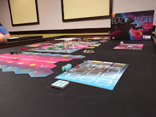 The game Black Angel ready to be played. The main board is seen in the midground, with the chevron-shaped tiles forming the modular space-travel board on which the Black Angel spaceship figure sits. The box sits in the background.
