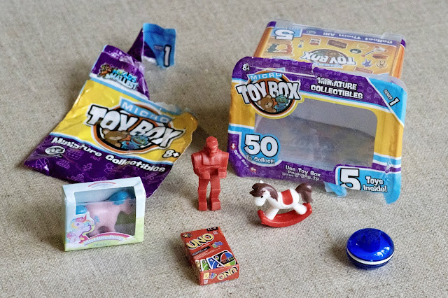 An example of 5 miniatures which might be in the surprise bag including My Little Pony, a yoyo, Uno, a robot and a rocking horse