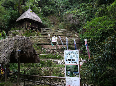 Nipa huts with bamboo bridge inside Tam-awan Village
