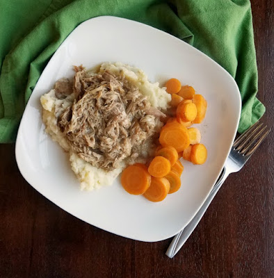 slow cooker apple cider pulled pork served on mashed potatoes with cooked carrot slices on the side