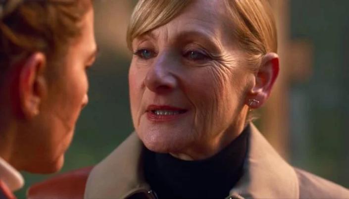 Imagem: a personagem Rosalind, interpretada por Lesley Sharp, uma mulher de meia-idade branca, os cabelos loiro-castanhos, olhos brilhantes em roupas sóbrias e em tom marrom conversando com outra personagem.