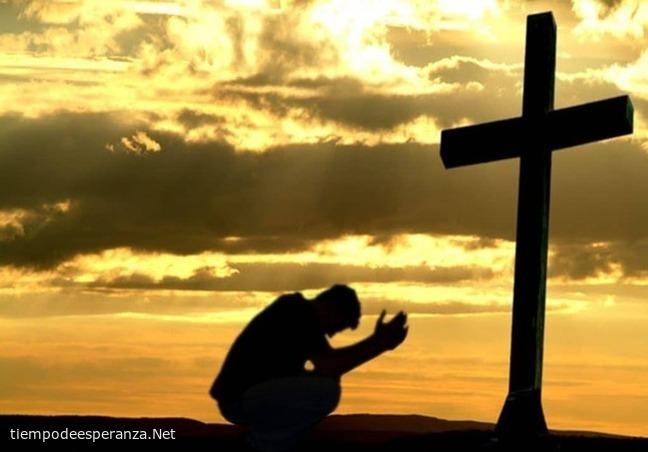 Cristiano orando frente a una cruz