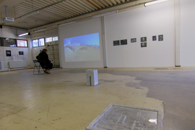 a general view of the show taken with a fish eye lens.A video work shows a ferris wheel, with small photographs on the right side, a person sitting in front of the video, and more works far on the left. The floor shows wear and is maybe laminate, tinting towards yellow.