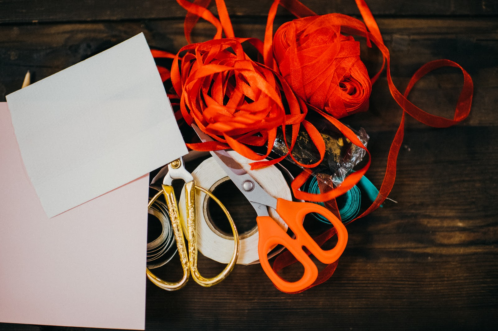 A flat lay of gold scissors and various ribbons, tape and card.