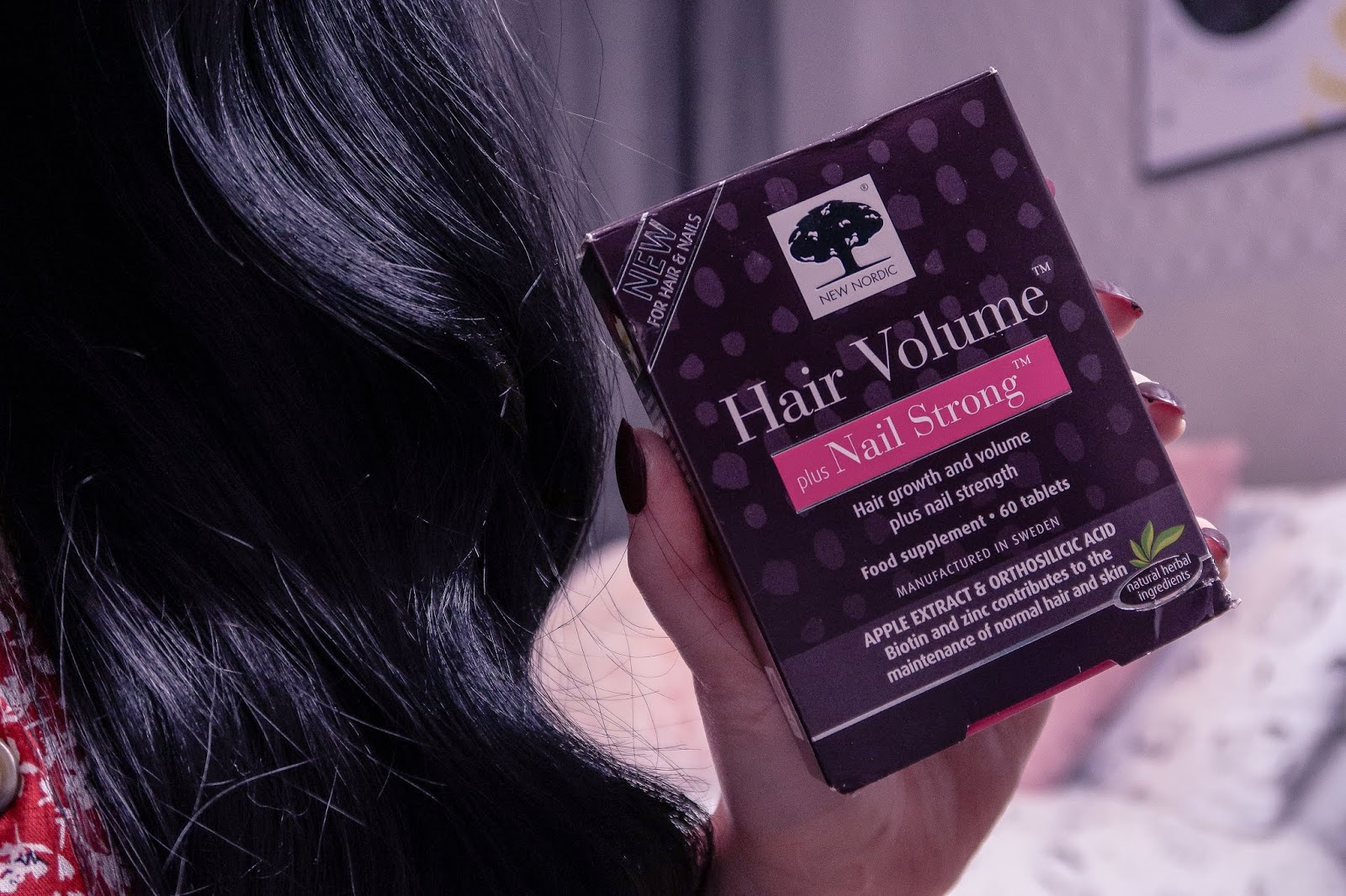 Close up photo of girl holding New Nordic Hair Volume plus Nail Strong Supplements - Wearing a red dress with white flowers, long black curled hair over left shoulder, New Nordic Supplements box is dark purple with white writing.