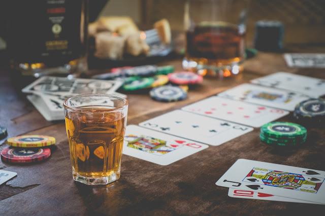 cachaça especial ao lado de baralhos e fichas de poker