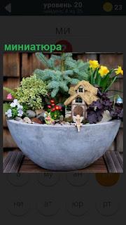 В миске сделана небольшая миниатюра цветы с маленьким домиком
