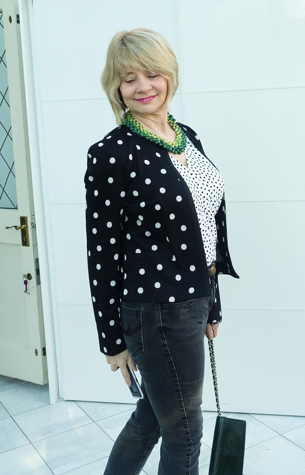 Dressing down a polka dot jacket with jeans and white boots