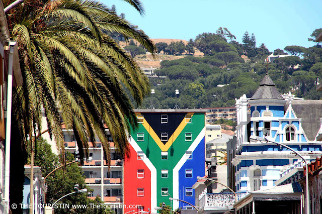 Red, white, green, yellow, black, blue South African Flag on a house facade.
