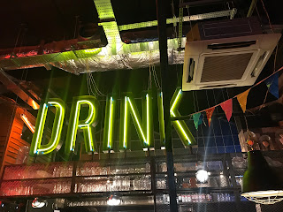 yellow neon sign saying DRINK