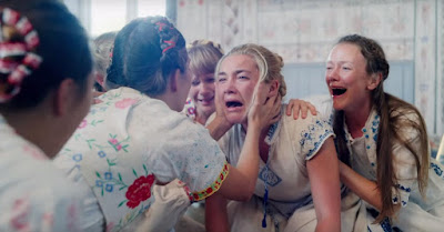 Florence Pugh cries on the floor surrounded by Swedish women in a movie still for Ari Aster's horror film Midsommar