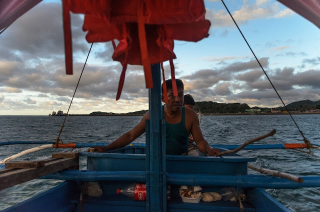 Leaving San Vicente Port and wharf at the background riding a motorized outrigger boat Philippines
