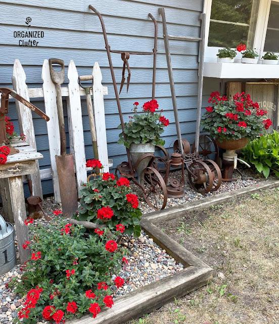 Foto de decoração antiga de fazenda e gerânios vermelhos