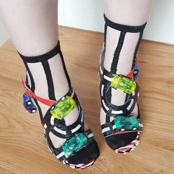 wearing sandals with road themed straps and toy cars