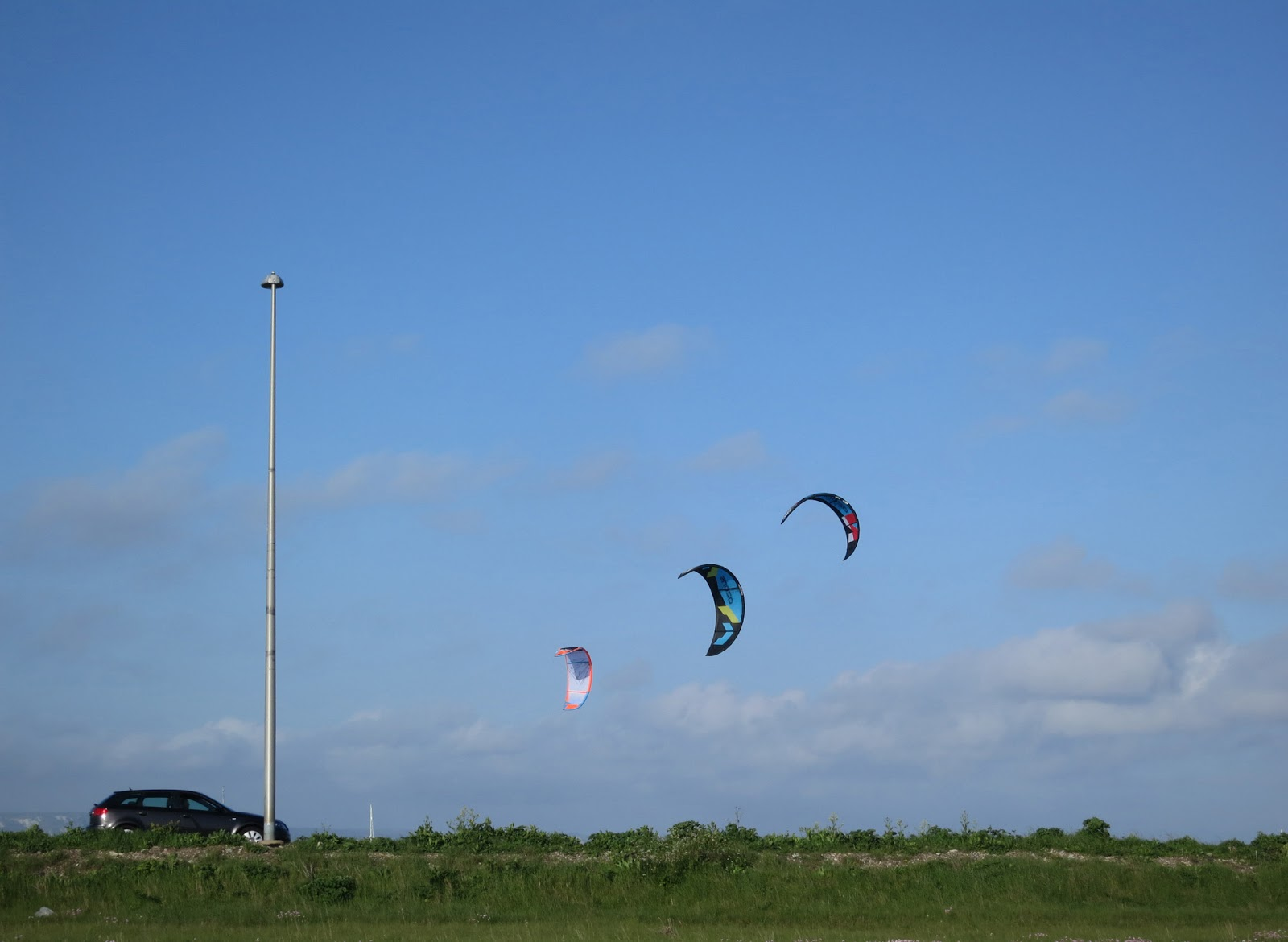 A car, a lampost and three kite-surfing canopies.