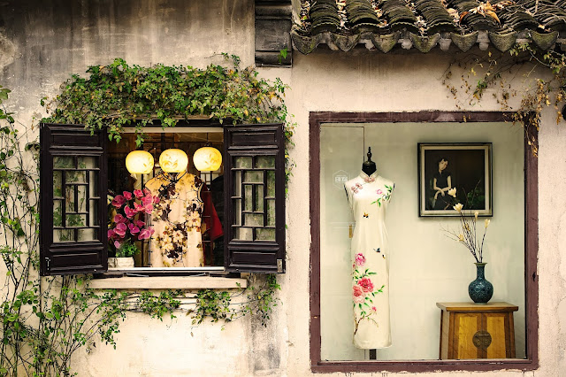 A shop's window displaying showing a traditional Chinese dress.