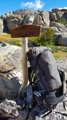 A backpack rests against the sign at Lester Pass in the Wind River Range of Wyoming, USA.