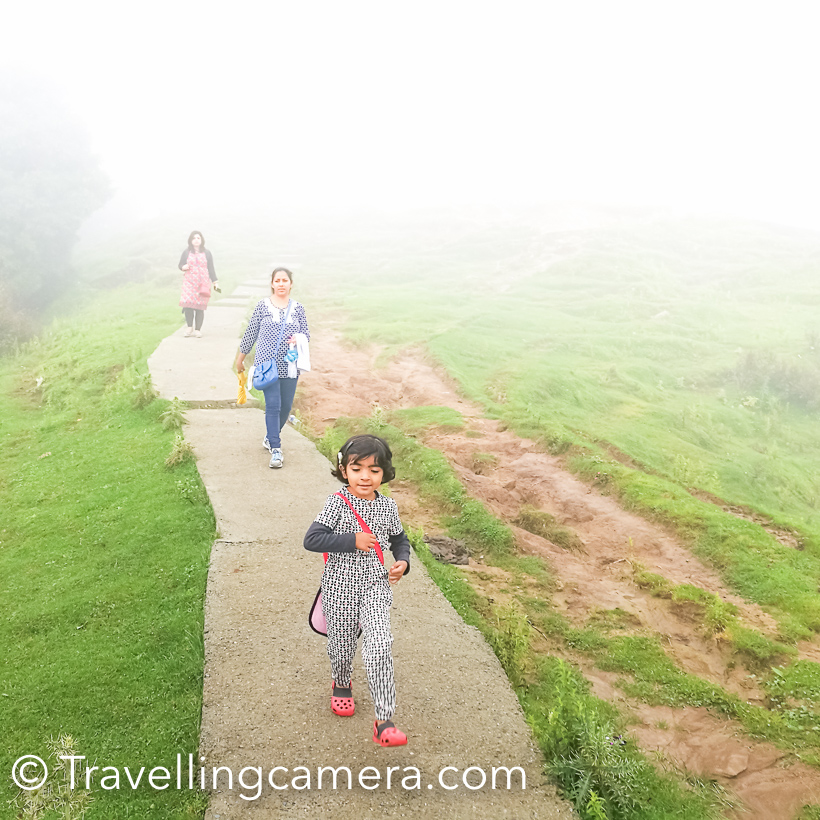 During my recent visit to Dalhousie, we planned to do a small trek to Dainkund (Temple Pohlani). This Photo Journey shares about our experience through clouds and how we beaten the rain. And if you are in Dalhousie during Monsoon, this trek is highly recommended. You literally walks through clouds and it's an easy trek.We drove through Kala Top to the base of this trek, which is entry gate of Air force base. We parked our car there and started the trek. There is well paved path for 1 km, which is maintained by temple authority. This path certainly made our lives easy during monsoons.This is a view after walking up for 250 meters. This road goes down to Dalhousie and Kala Top.As we started the trek, rain started and we thought of skipping it and going to Khajjiar instead. But in few minutes we encouraged each other to use umbrellas and start climbing up. And at the end it proved to be rewarding.Clouds were playing hide and seek with us. At times, they were chasing us and in few minutes sun was shining by clearing them away.Throughout the trek you are exposed to some breathtaking views of valley full of high deodars and birds flying all around. We saw few colorful butterflies on our way but couldn't click them well.We did the trek at our own pace. Stopped many times and enjoyed quick snacks which we were carrying with us. And Urvi was always ready to pose :)On the way, there is a temple which is 2.5 kilometers away from road. Lot of local folks visit this temple. Interesting most of the temples in this region don't have roofs. There is a little shop near the temple from where you can buy snacks and juices.While walking through the mountains, Vibha pointed towards this cloud form. With a smile she says - 'doesn't it look like a giraffe?'. Do you think so?There is a beautiful view through clouds. Most of the times clouds stopped our view of surroundings but such views through clouds were very special.This is 3 kilometers trek which means you need to walk for 6 kilometer