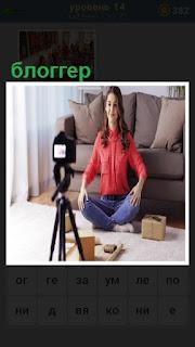 на полу сидит блоггер перед фотоаппаратом и делает селфи