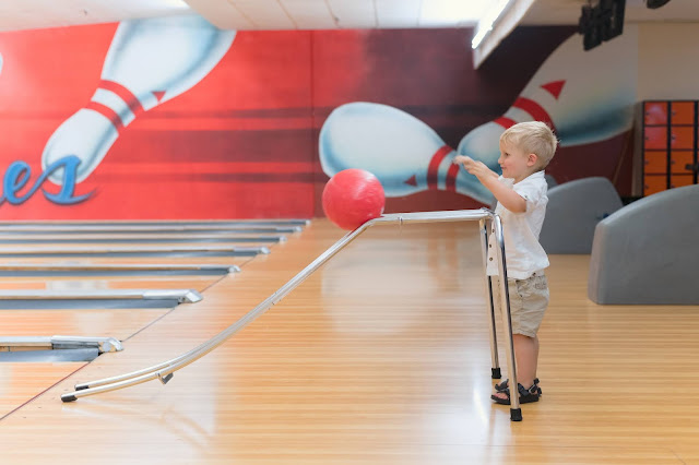 A small boy using a bowling aid in a bowling alley
