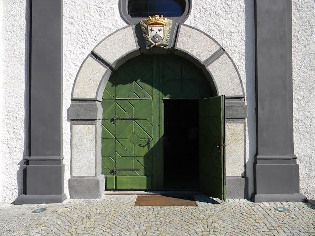 Do zamku prowadzą zadbane, zielone drzwi.