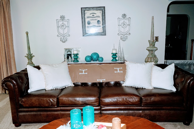 Living room with decorative iron pieces on wall, chesterfield sofa, pillows, coffee table