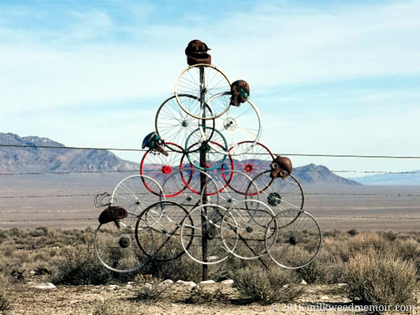 "16 bicycle rims are mounted to a fence post in a triangle formation, along with a few vaguely human heads. This is an example of whimsical ""post impression art,"" a hobby of sorts for residents of Baker, Nevada."