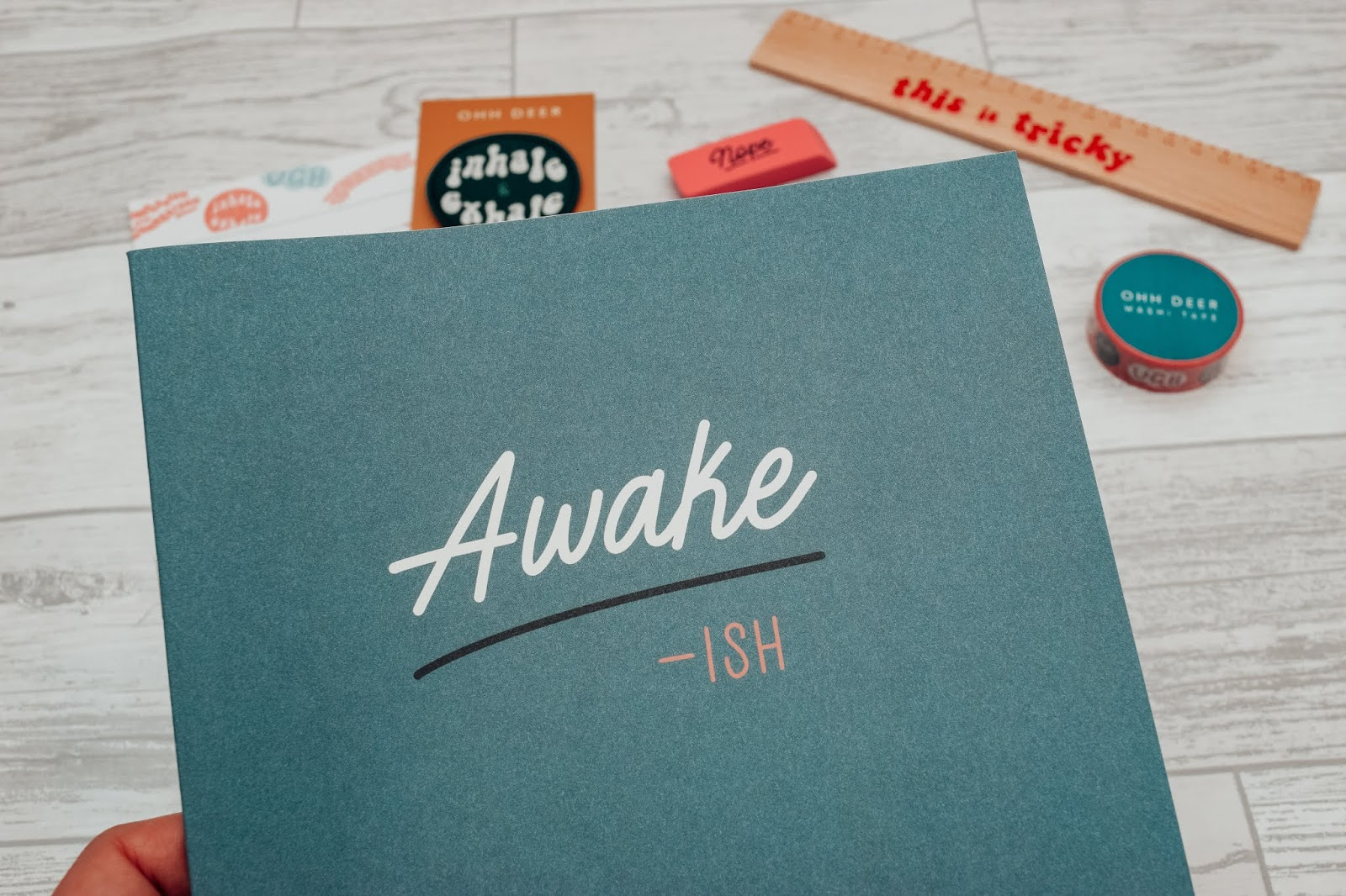 A blue notebook with the word Awake-ish on the front.