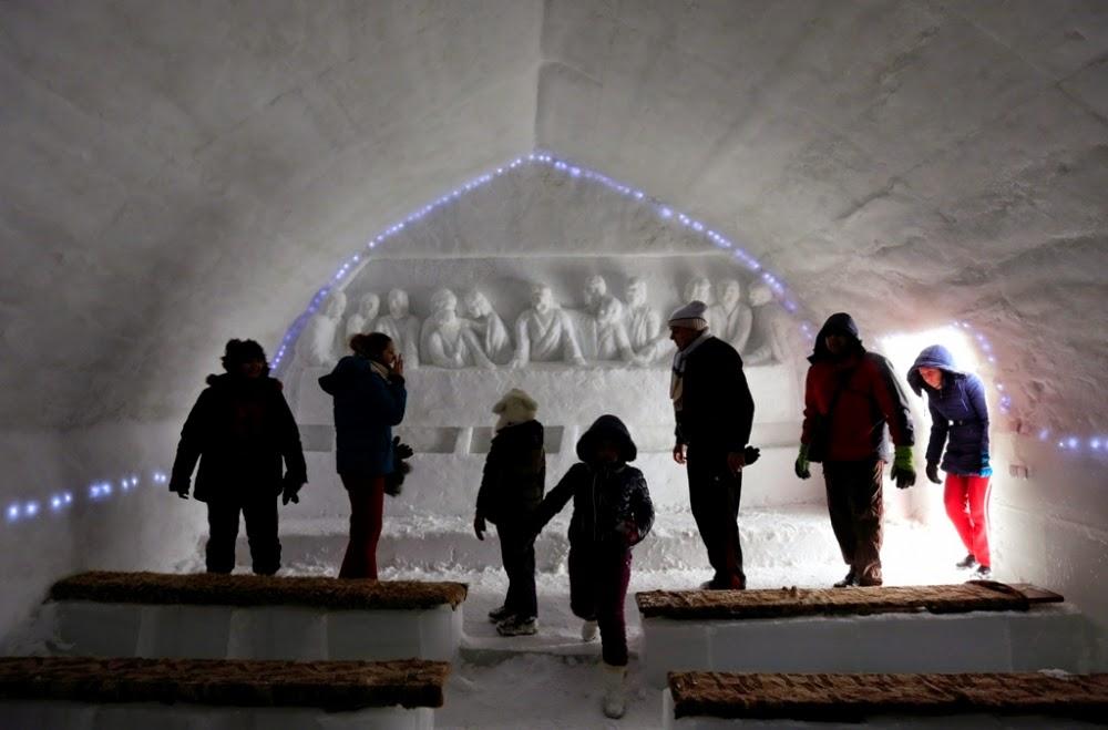 Turişti care păşeşc în faţă spre a vedea sculptura de gheaţă ce înfăţişează Cina cea de Taină în cadrul bisericii de gheaţă de la Bâlea Lac - foto credit: Reuters/Radu Sigheti