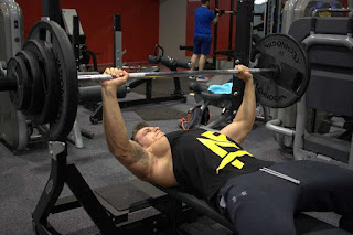 Bodybuilder using the bench press at the gym
