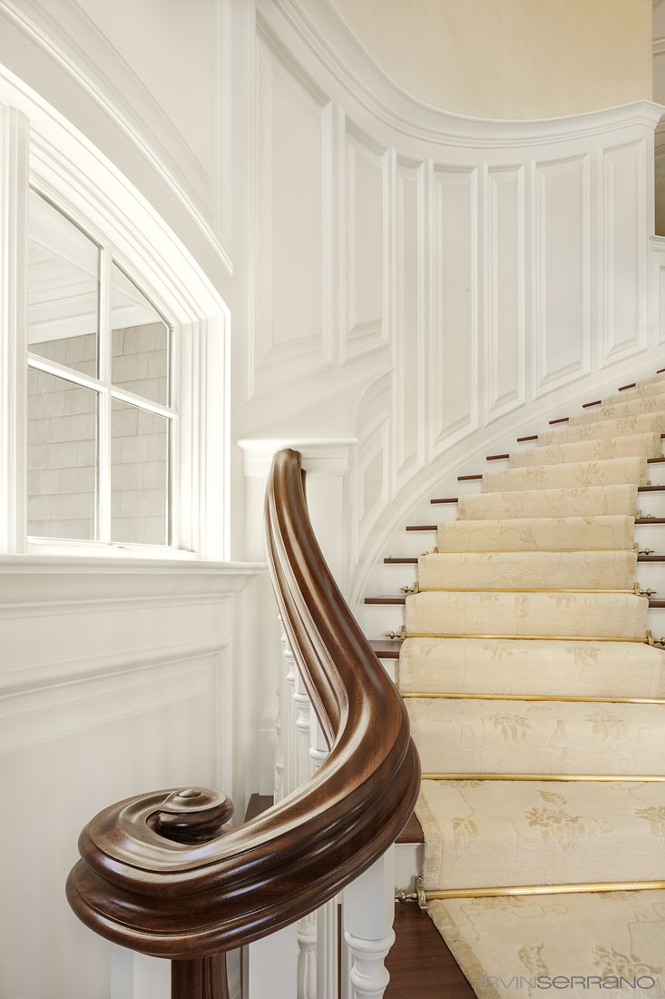 One side of a double staircase shows curved paneling and a mahogany railing and volute designed by Knickerbocker group and executed by Tidewater Millwork.