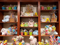 small pastel buckets full of candy, easter grass, and cellophane sit on wooden shelves with rabbit, lamb, and duck plush animals at Palmer's Candy in Sioux City, Iowa