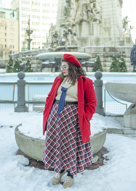 An outfit consisting of a red beret, a red coat, a cream cowl neck sweater, a navy ribbon tied under the cowl into a bow, and a red, blue and white plaid skirt.
