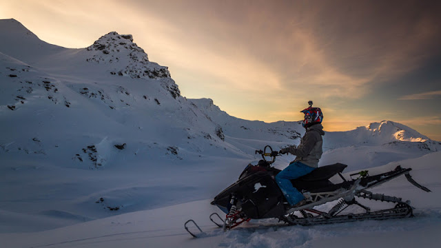 solo snowmobile rider watching the sun rise from behind the mountains