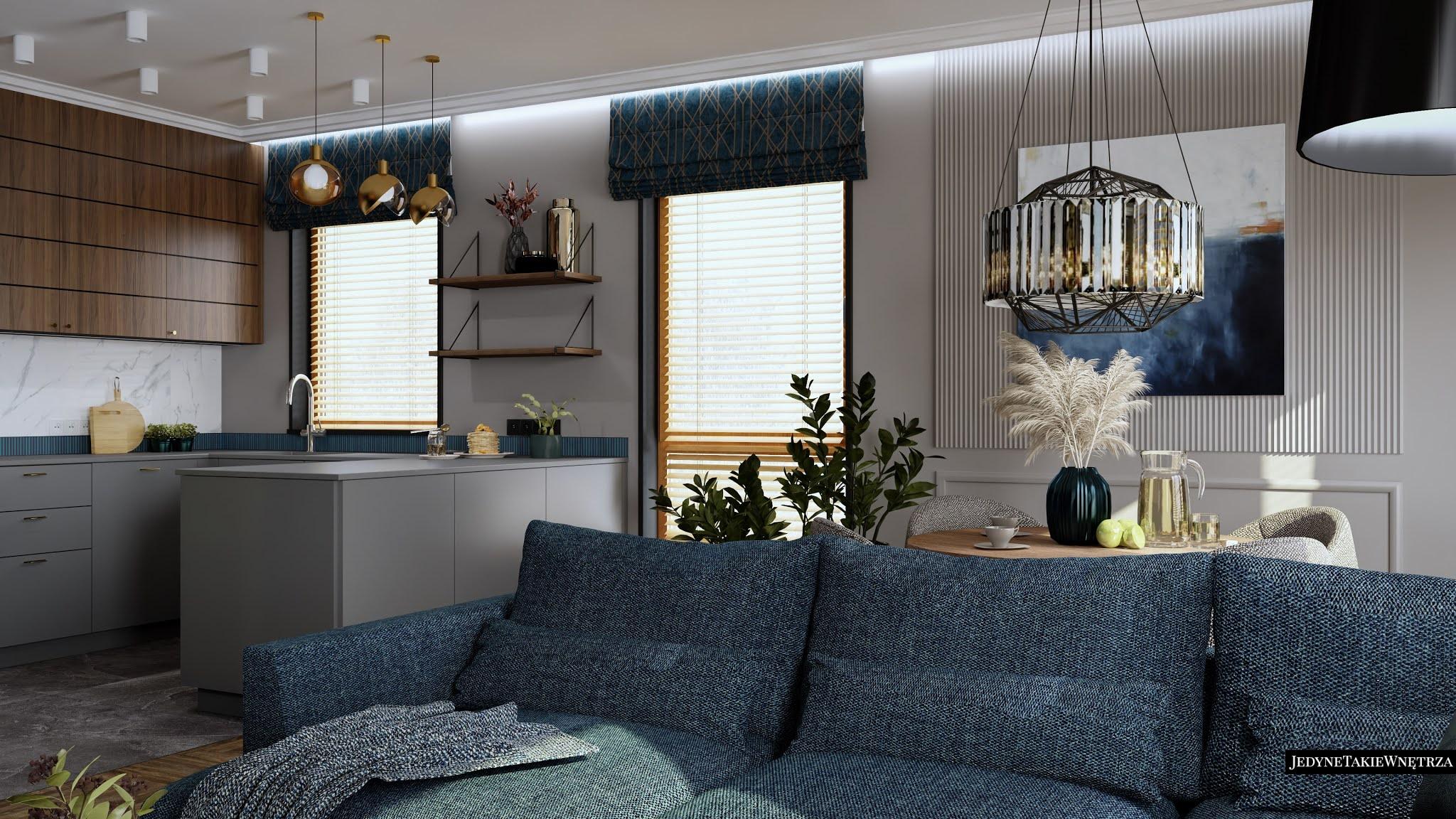Nowoczesny salon z kuchnią. Na ścianie płytki imitujące marmur, drewniano-szare meble w kuchni. Wnętrze zdobi luksusowy żyrandol.