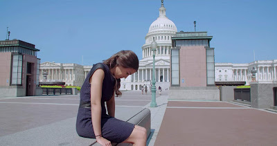 Movie still for Netflix's film Knock Down the House where Alexandria Ocasio-Cortez sits outside the United States Capitol building and reflecting after winning an election to become the U.S. Representative for New York's 14th congressional district